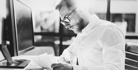 Bearded young businessman working at modern office.Man wearing white shirt and making notes on the documents.Panoramic windows background. Horizontal, film effect.Blurred, black and white.