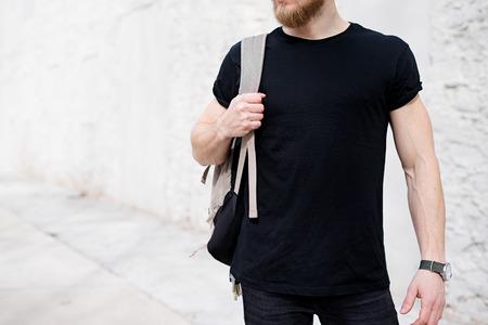 검은 티셔츠와 배낭 밖에 서 포즈를 입고 젊은 근육 질의 남자. 배경에 빈 흰색 콘크리트 벽입니다. 수평으로 만든 모형, 정면보기 스톡 콘텐츠
