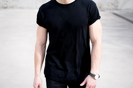 black t shirt: Closeup view of young muscular man wearing black tshirt and jeans posing outside. Empty background. Hotizontal mockup.