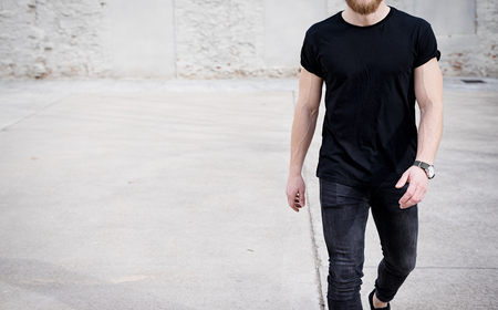Young muscular man wearing black tshirt and jeans walking on the urban district. Blurred background. Hotizontal mockup.