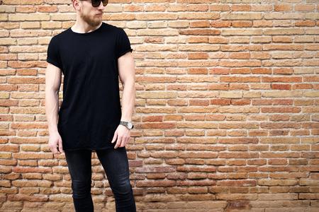 외부 포즈 블랙의 tshirt, 선글라스와 청바지를 입고 젊은 근육 남자. 배경에 빈 갈색 그런 지 벽돌 벽입니다. Hotizontal 모형.