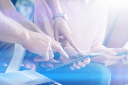 Closeup view of two hands pointing on digital tablet.Young business team working with new startup project.Blurred background, visual effect. Horizontal