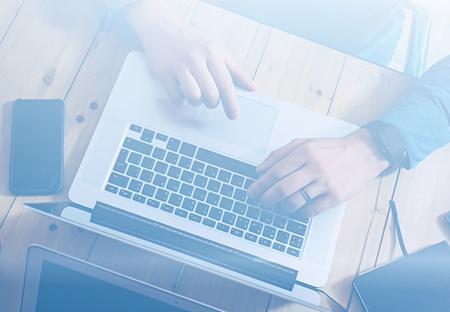 랩톱에 나무 테이블에서 작동하는 사업가. 노트북 키보드에 남자 문자 .Horizontal, visual effects.Top보기입니다.
