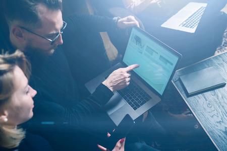 Coworking proces office.Two jonge collega's met behulp computer.Woman dragen zwarte trui en zitten op de sofa.Graphs en diagram op de laptop screen.Horizontal, visuele effecten. Stockfoto