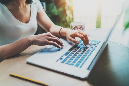 Jonge vrouw die thuis aan moderne computer werkt Meisje die op laptop toetsenbord typen terwijl het zitten bij de houten lijst Concept jonge moderne mensen die mobiele apparaten thuis met behulp van Vage achtergrond. Stockfoto