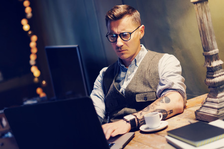 Pensive tattooed man in eyeglasses working at home on laptop while sitting at the wooden table.Using modern computer for research new startup ideas.Concept of business people work.Blurred background.