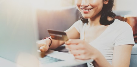 Happy attractive Asian woman using laptop and golden creditcard for online shopping from home.Blurred background,flares effect. Wide. Stock Photo