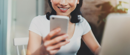 domicile: Young smiling Asian woman spending rest time at home and using smartphone for texting with friends.Selective focus. Blurred background, flares effect, wide. Stock Photo
