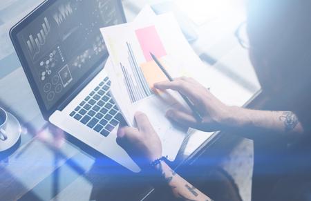 Close-up beeld van volwassen getatoeëerd collega werken met laptop op werkplek. Zakenman analyseren van documenten op handen. Grafieken, online interfaces, diagramm op laptop scherm. Horizontale, wazig
