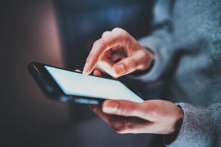 Close-up beeld van smartphone in handen te houden. Vrouwelijke vingers aanraken van witte leeg scherm. Horizontale, onscherpe achtergrond. Stockfoto
