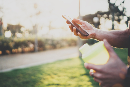 Workout lifestyle concept.Muscular handsome athlete checking training programm on smartphone application after good workout session on city park in the sunny morning.Blurred background. Stock Photo