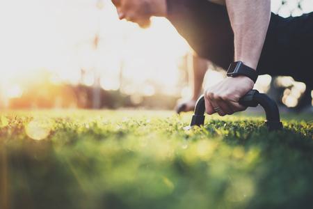 Concepto de estilo de vida saludable. El ejercicio del atleta muscular empuja hacia arriba afuera en el parque soleado. Ajuste el modelo masculino descamisado de la aptitud en ejercicio del crossfit al aire libre. Hombre de la aptitud del deporte que hace pectorales. Fondo borroso. Foto de archivo - 74628116