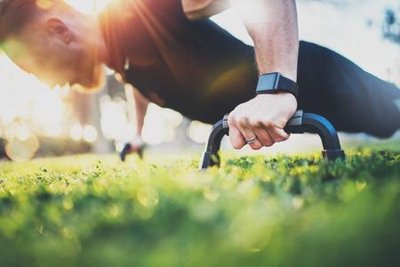 健康的なライフ スタイルのコンセプト。屋外のトレーニング。ハンサムなスポーツ男は晴れた朝に公園で腕立て伏せ。背景をぼかし。 写真素材