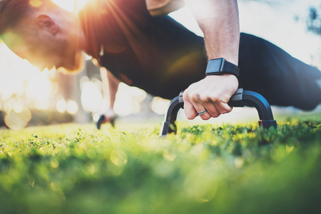 Stile di vita sano concept.Training outdoors.Handsome di uomo sportivo facendo flessioni nel parco la mattina di sole. sfondo sfocato.