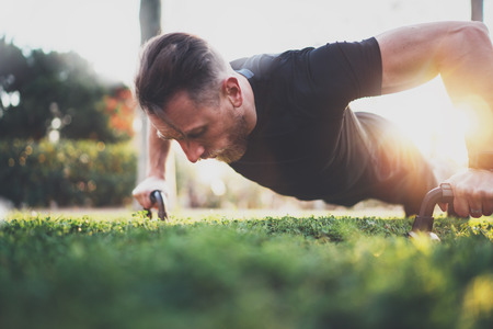 Muscular athlete exercising push up outside in sunny park. Fit shirtless male fitness model in crossfit exercise outdoors.Sport fitness man doing push-ups.Blurred background.