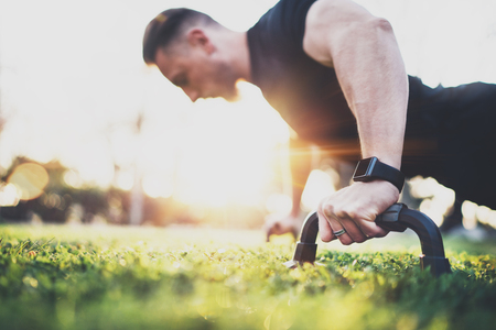 Workout lifestyle concept.Muscular athlete exercising push up outside in sunny park. Fit shirtless male fitness model in crossfit exercise outdoors.Sport fitness man doing push-ups.Blurred background.