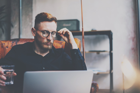 Pensive bearded businessman in eyeglasses working at modern loft.Man sitting in vintage chair,holding in hands glass of water,using contemporary notebook.Blurred background,flares.Horizontal
