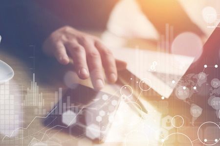 Concept of digital screen,virtual connection icon,diagram,graph interfaces.Businessman working at sunny office on laptop and smartphone while sitting at the wooden table.Sunlights effects.Blurred. Zdjęcie Seryjne