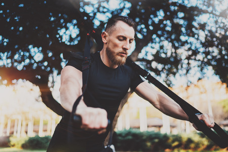 Muscular athlete exercising trx push up outside in sunny park.Fit shirtless male fitness model in crossfit exercise outdoors.Sport fitness man doing push-up workout.Blurred background.Wide horizontal.