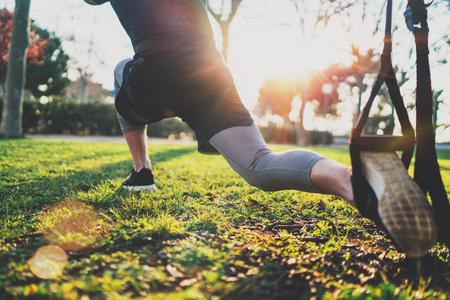 あなたの強さの概念を感じる。日当たりの良い公園の外の trx を行使の若い選手。偉大な TRX トレーニング。屋外で運動を行うスポーツ ウエアでハン