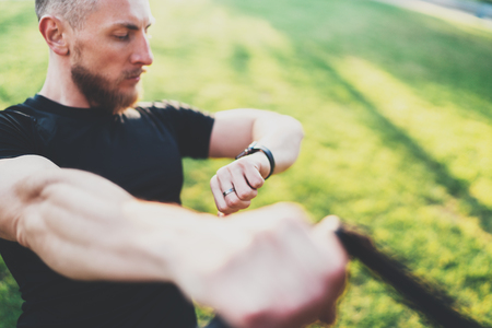 Healthy smart lifestyle concept.Muscular athlete doing great exercising TRX outside in sunny park.Young handsome man in sportswear checking sport tracker watch.Blurred background. Stock Photo
