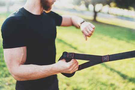 Healthy smart lifestyle concept.Muscular athlete doing great exercising TRX outside in sunny park.Young handsome man in sportswear checking sport tracker watch.Selective focus on hand.Blurred.