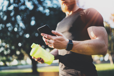 programm: Workout smart fitness concept.Young Muscular athlete checking training programm on smartphone application after perfect workout session at sunny morning.Blurred background.