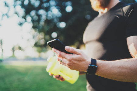 programm: Workout fitness concept.Closeup view of Muscular athlete checking training programm on smartphone application after perfect workout session at sunny morning.Blurred background.