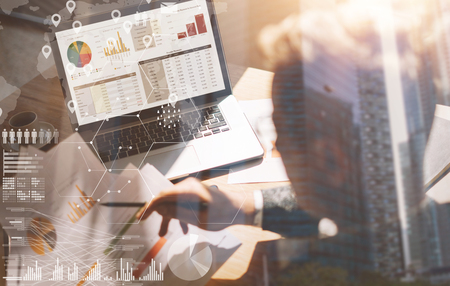 Businessman working at office on laptop.Man holding paper documents in hands.Concept of digital screen,virtual connection icon,diagram,graph interfaces on background.Double exposure,closeup. 版權商用圖片
