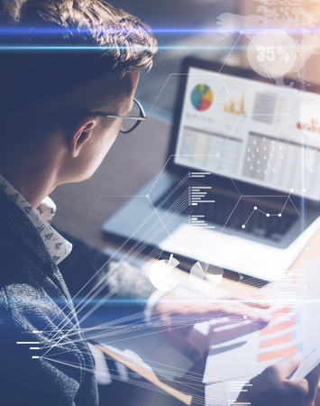 젊은 사업가 노트북 화면에 주식 보고서를 분석합니다. 디지털 화면, 가상 연결 아이콘, 다이어그램, 배경에 그래프 인터페이스의 개념. 수직. 스톡 콘텐츠