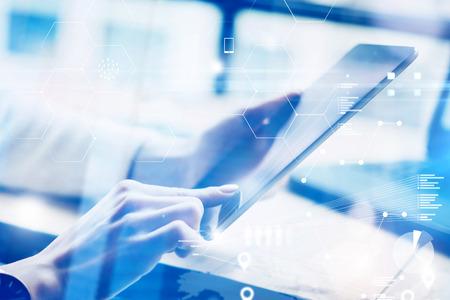 Gros plan de mains féminines tenant une tablette numérique moderne. Gens d'affaires de concept à l'aide de gadgets mobiles.Icon et graphiques sur l'écran de fond.Effet visuel, flou.Horizontale. Banque d'images