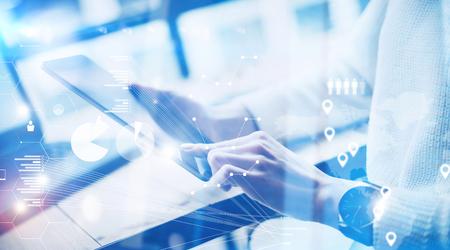 Concept van het virtuele scherm, digitale verbindingspictogram en grafiekinterfaces. Jonge onderneemster die aan moderne mobiele tablet werken terwijl het zitten op het werkplaats op zonnig kantoor Vage achtergrond.