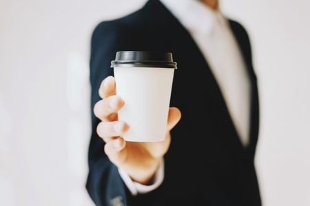 Businessman holding white paper coffee cup to take away.Mock up of carton coffee cup for go outside.Horizontal mockup, blurred background.