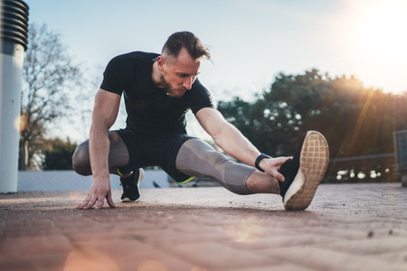 outdoor outside: Outdoor Workout lifestyle concept.Young fitness man doing stretch exercises muscles before training.Muscular athlete exercising outside in sunny park. Blurred background.Horizontal.