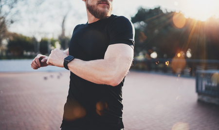 outdoor outside: Outdoor Workout lifestyle concept.Young man stretching his body muscles before training.Muscular athlete wearing smart watch on hand exercising outside in sunny park. Blurred background.