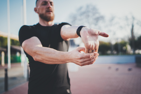 Workout outdoor lifestyle concept.Young man stretching his arm muscles before training.Bearded Muscular athlete exercising outside in sunny park. Blurred background.