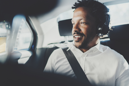 Handsome smiling african man listening music on smartphone while sitting on backseat in taxi car.Concept of happy young people traveling in the city.Blurred background.