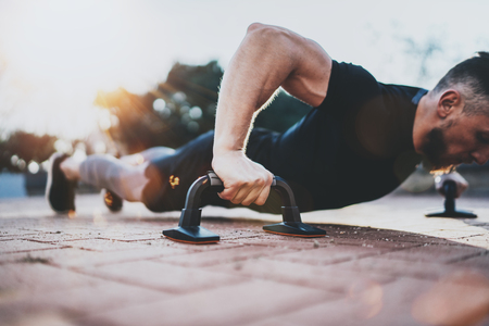 Healthy lifestyle concept.Training outdoors.Handsome sport athlete man doing pushups in the park on the sunny morning. Blurred background.