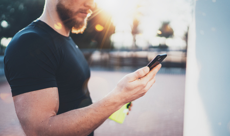 Closeup view of Muscular handsome athlete checking sport results on smartphone application and smart watch after good workout session on city park in the sunny morning.Blurred background. Stock Photo