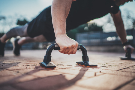 Closeup view of Handsome sport man doing pushups in the park on the sunny morning.Healthy lifestyle concept.Training outdoors.Blurred background.