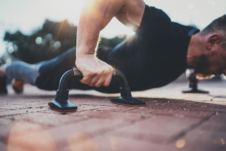 Healthy workout lifestyle concept.Training outdoors.Handsome sport athlete man doing pushups in the park on the sunny morning. Blurred background. Stock Photo