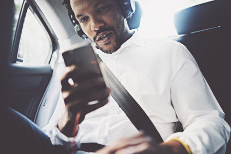 Young smiling african man using smartphone while sitting on backseat in car.Concept of happy business people traveling.Blurred background.