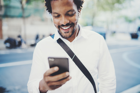 Portrait of Happy African American man in headphone walking at sunny city and enjoying to music on his smartphone.Concept of guy using Internet-enabled electronic device,texting friends.Blurred.