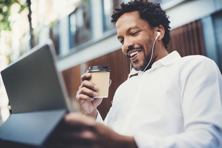 Uomo afroamericano felice in auricolari che fanno videochiamata tramite il touchpad elettronico con porta via il caffè a disposizione. Concetto del tipo che utilizza il dispositivo elettronico Internet-permesso fuori Priorità bassa vaga. Archivio Fotografico - 77836067