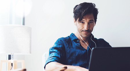 Handsome adult man working at home.Man using contemporary notebook on headphones while sitting in vintage chair.Blurred background. Horizontal wide.Crop.