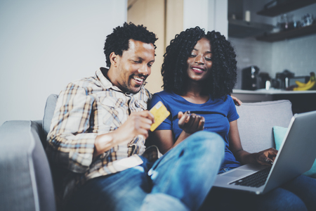 Smiling young african american couple shopping online through modern laptop using credit card at home. Horizontal,blurred background.