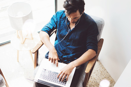 Top view of young man working at home.Man using contemporary laptop and headphones while sitting in vintage chair.Blurred background. Horizontal.