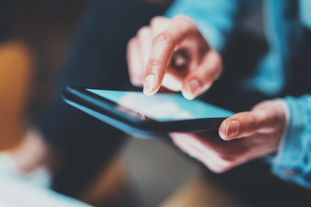 touch screen: Closeup view of woman holding modern smartphone in hands.Girl typing on white touch mobile screen. Horizontal, blurred background, bokeh effects.Macro.