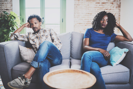 Young displeased black couple.American african men arguing with his stylish girlfriend,who is sitting on sofa on couch next to him with legs crossed.Man looking away offended expression on her face.