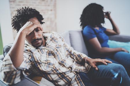 Jong triest zwart paar. Verstoorde mens die door partner thuis in de woonkamer worden genegeerd. Amerikaanse Afrikaanse mensen die met zijn modieus meisje debatteren, die op banklaag naast hem zit.